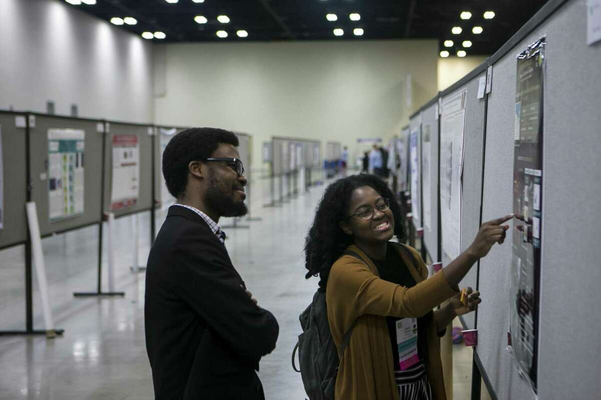 Omase Omoruyi shares her research on star formation with Chukwunoso Arinze on Friday during the 45th annual National Diversity in STEM Conference. The conference was sponsored by the Society for the Advancement of Chicanos/Hispanic & Native Americans in Science at the Henry B. Gonzalez Convention Center.