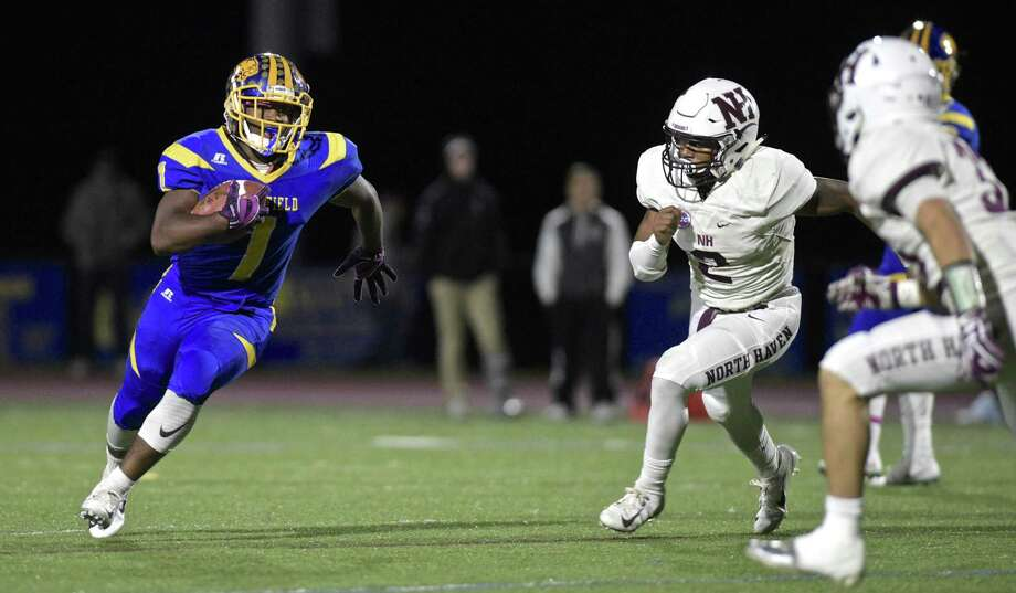 Brookfield's Nick Henderson (1) goes around the outside with North Haven's Albert Hooks (2) and Devan Brockamer (32) waiting in the football game between North Haven and Brookfield high schools, Friday night, October 12, 2018, at Brookfield High School, Brookfield, Conn. Photo: H John Voorhees III / Hearst Connecticut Media / The News-Times