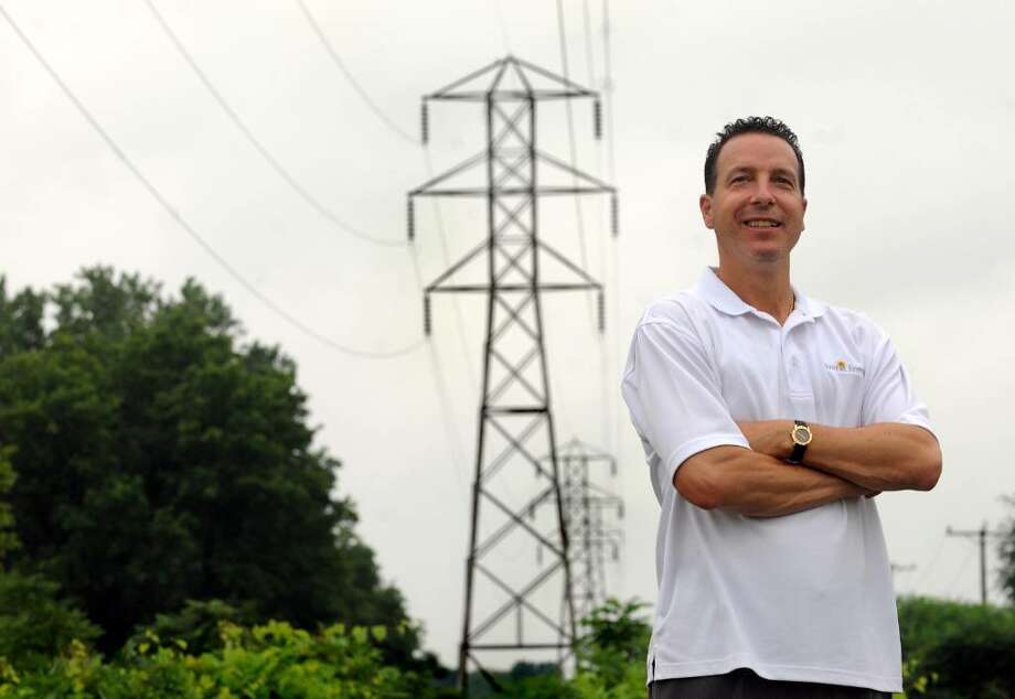 Greg Henzel of Ambit Energy stands by a transmission line tower on Wednesday, July 14, 2010, in Colonie. (Cindy Schultz / Times Union) Photo: CINDY SCHULTZ