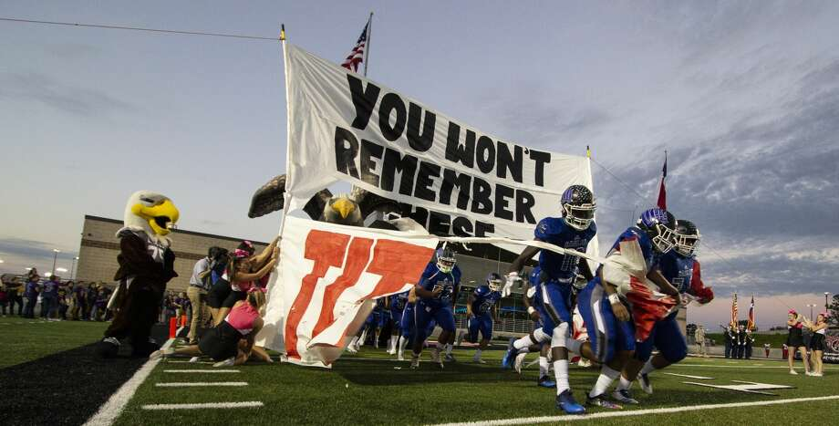 "The New Caney Eagles break through a sign with ""You won't remember these Titans"" written on it before a District 9-5A (Div. I) football game Friday, Oct. 12, 2018 at Texan Drive Stadium in New Caney. Photo: Cody Bahn/Staff Photographer"