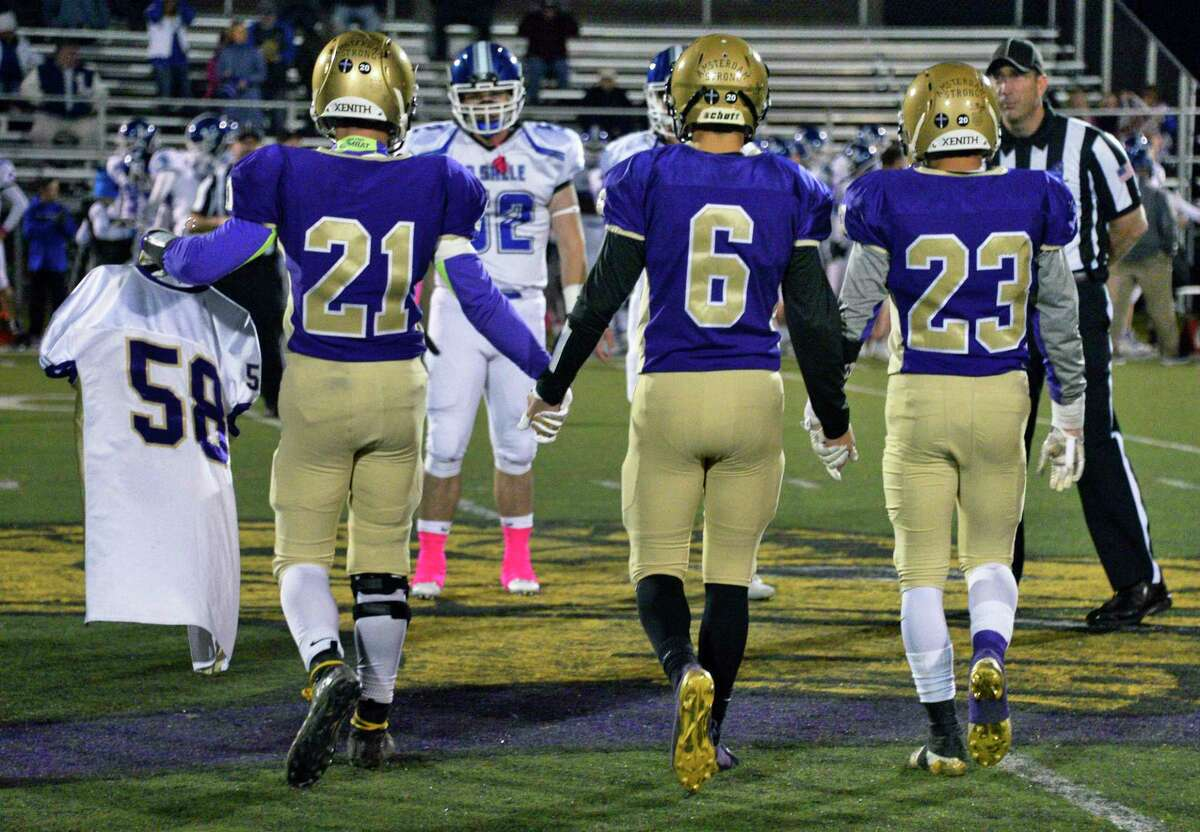 """Amsterdam High team captains, from left,Trey Ausfeld, Andrew Giaimo and Peyton Ausfeld carry the jersey of alum Adam """"Action"""" Jackson, a victim of the Schoharie limo crash to the coin toss at the start of their game against La Salle Friday Oct. 12, 2018 in Amsterdam, NY. (John Carl D'Annibale/Times Union)"""