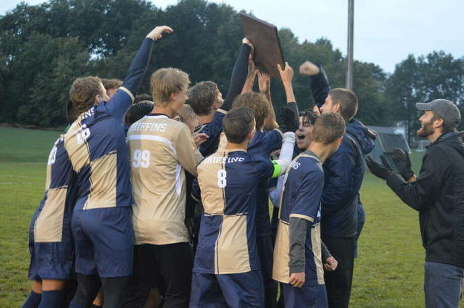 The Father McGivney boys' soccer team celebrates with the championship plaque after Friday's 3-1 win over East Alton-Wood River in the title game of the Class 1A Greenville Regional. Photo: Scott Marion/Intelligencer