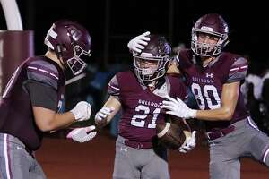 Magnolia's Kade Bond (70), Mitch Hall (21) and Aidan Garrigan celebrate Hall's touchdown against Willis during the first half of their game Friday, Oct. 12, 2018 in Magnolia, TX.
