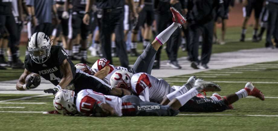 Justin Hammond (4) is tackled by Odessa players after a run Friday night at Ratliff Stadium. Photo: Jacy Lewis/191 News