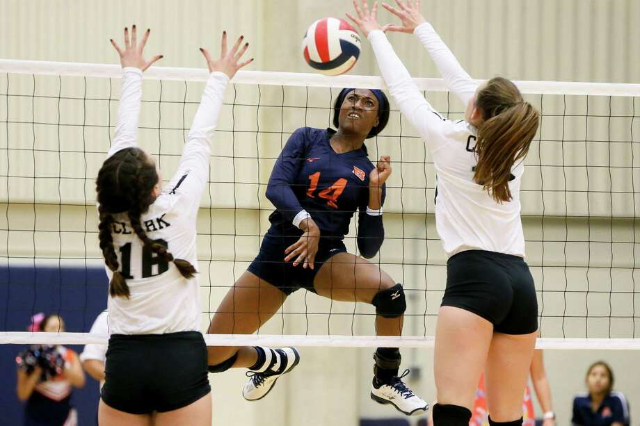 Brandeis' Chidera Ugwokaegbe (center) hits the ball between Clark's Micayla Reiland (left) and Grace Gibson during their District 28-6A high school volleyball match at Taylor Fieldhouse on Tuesday, Oct. 2, 2018. Clark won the match in five sets. Photo: Marvin Pfeiffer, Staff Photographer / Express-News 2018