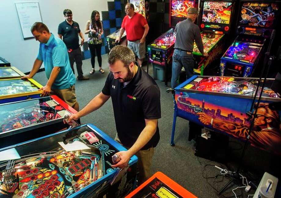 Game On owner Brian Stein, center, and Doug Lee of Midland, left, play pinball during a meeting of a local league on Tuesday at the store in Midland. (Katy Kildee/kkildee@mdn.net)