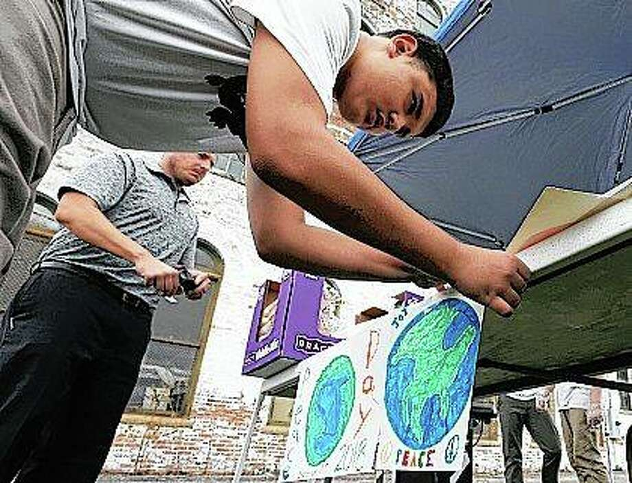 Student Jeffrey Binkley posts signs with truancy officer homeless liaison Kyle Bruce for International Peace Day during the Milligan Academy Safe School class' event to provide lunch for the less fortunate. Photo: Jim Bowling | Herald & Review (AP)