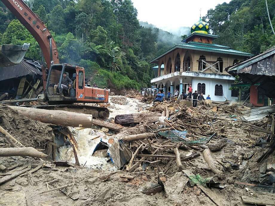 Workers clear debris after heavy rains led to flash flooding in Mandailing Natal district in North Sumatra province. Photo: Agus Salim / AFP / Getty Images