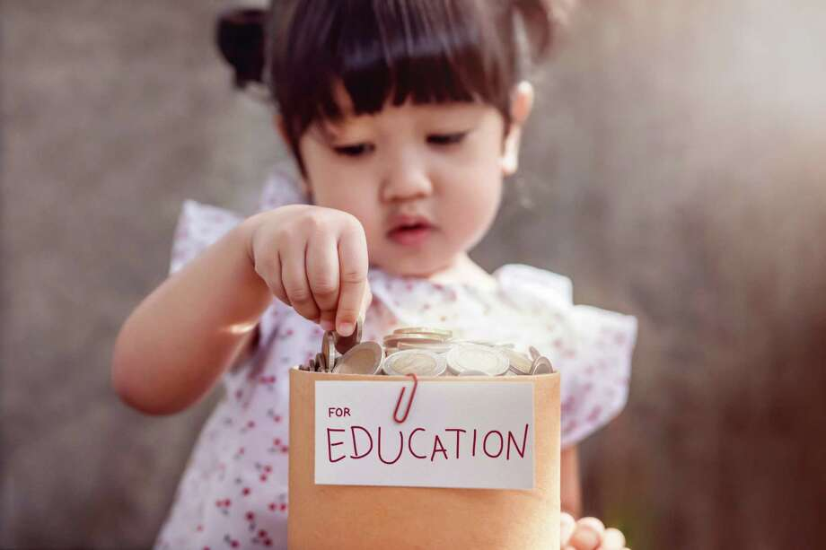Child with Saving Money for Education Concept. 2 Years Old Child putting Coin into a Box Photo: BlackSalmon / iStockphoto