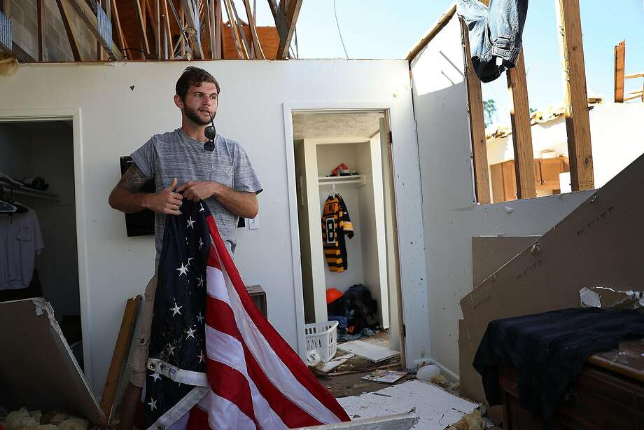 PANAMA CITY , FL - OCTOBER 13: Jacob Schmidt folds up an American flag as he salvages items from his apartment after it was destroyed by hurricane Michael on October 13, 2018 in Panama City, Florida. Schmidt said he was in the apartment when the storm hit and tore his home apart. The hurricane hit the Florida Panhandle as a category 4 storm causing massive damage. (Photo by Joe Raedle/Getty Images) Photo: Joe Raedle / Getty Images