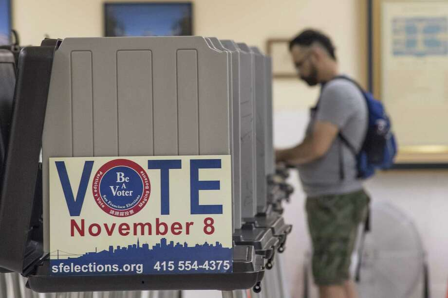 """A sign reading """"Vote"""" is displayed on the side of a booth as a voter casts a ballot in San Francisco on Nov. 8, 2016. Photo: Bloomberg Photo By David Paul Morris. / © 2016 Bloomberg Finance LP"""