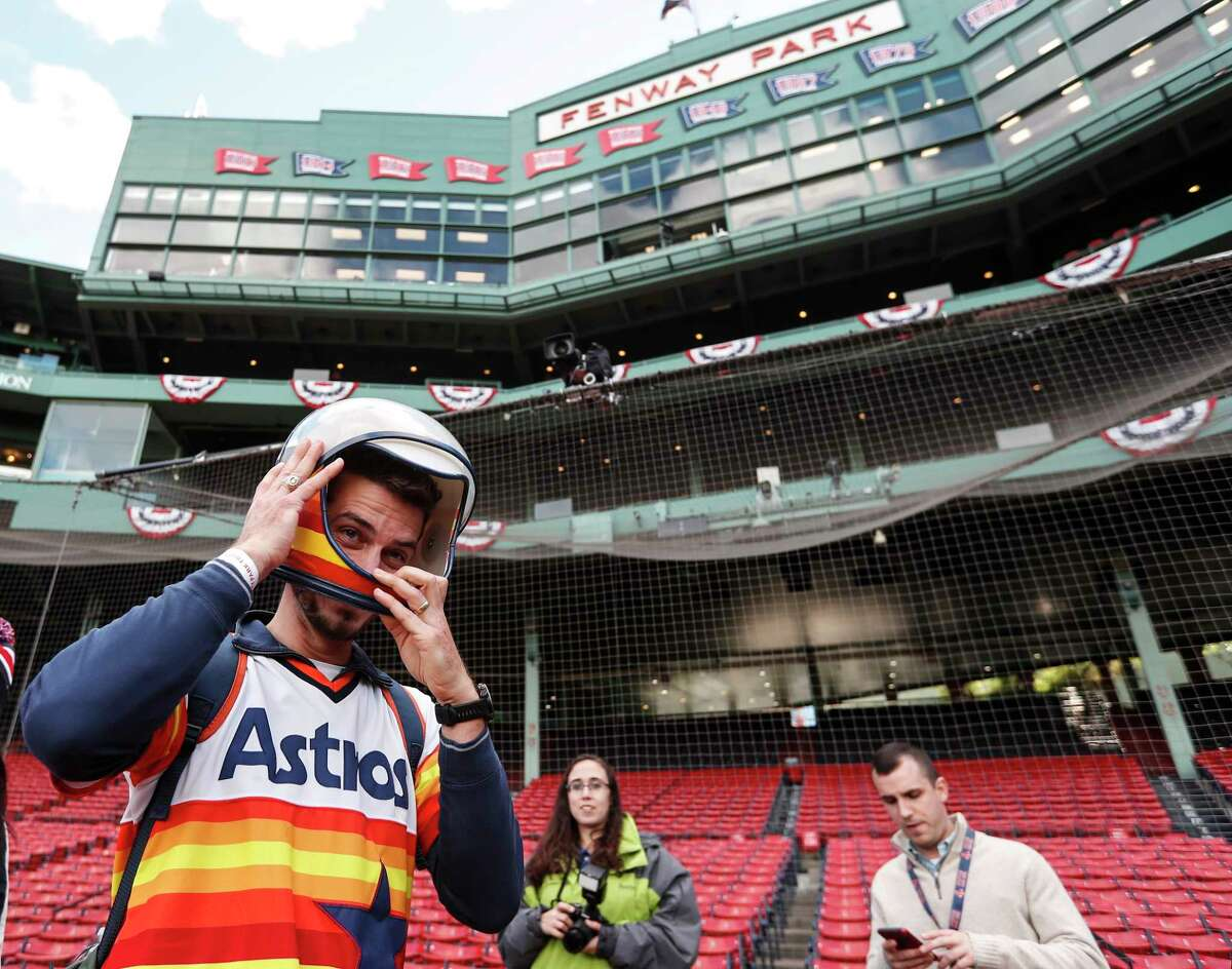 Houston Astros fan Simon Sattler dons a space helmet as he walks on the field while taking a tour of Fenway Park before Game 1 of the American League Championship Series on Saturday, Oct. 13, 2018, in Boston.