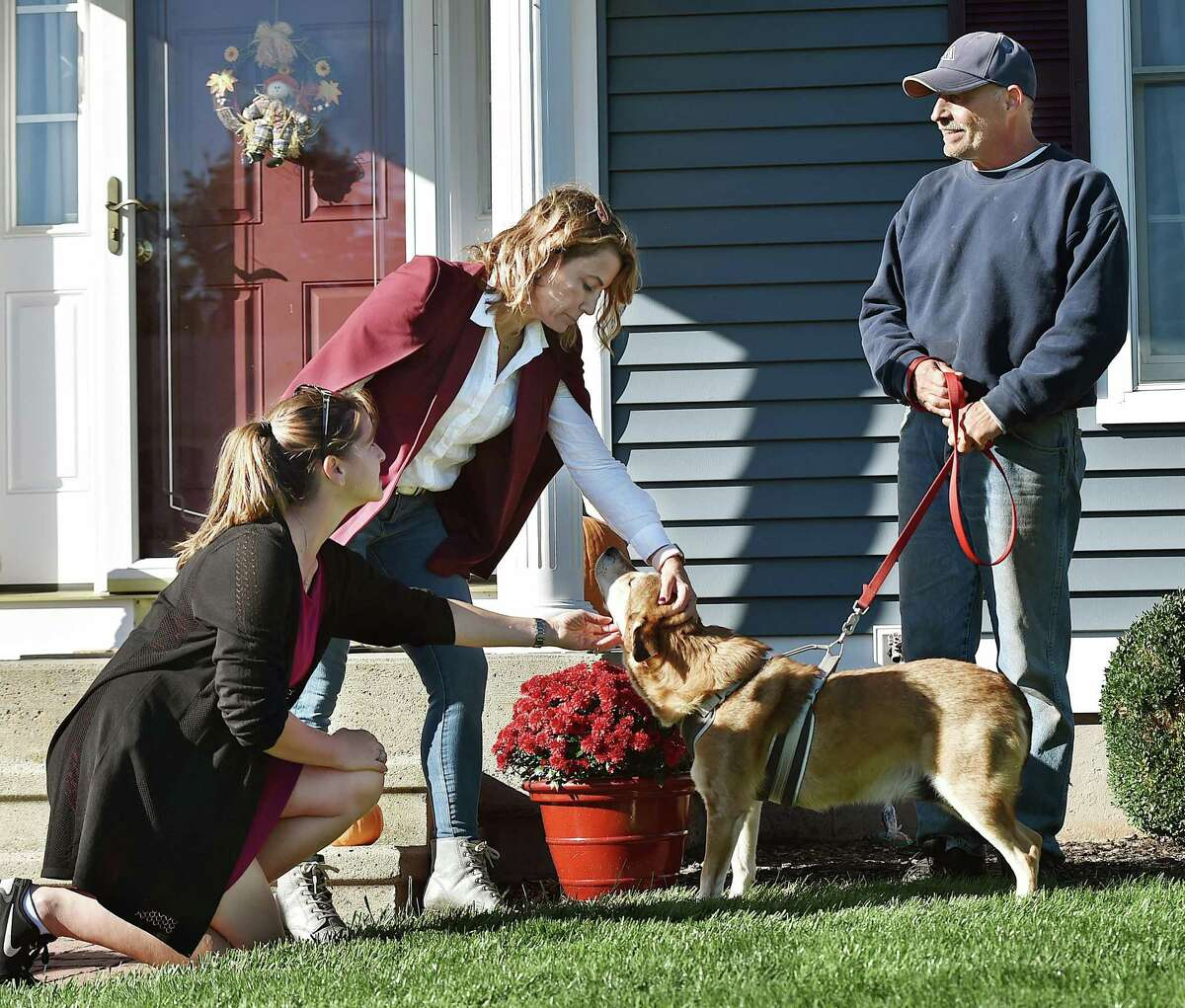House Minority Leader Themis Klarides, R-Derby joins State Rep. Christie Carpino, R-Cromwell pets Cooper while talking with Tom Grande campaigning door to door Friday, October 12, 2018, in Cromwell.