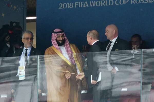 Mohammed bin Salman, Saudi Arabia's crown prince, center, shakes hands with Vladimir Putin, Russia's president, as Gianni Infantino, president of FIFA, right, look on after arriving for the opening ceremony for the FIFA World Cup at the Luzhniki stadium in Moscow, Russia, on June 14, 2018.