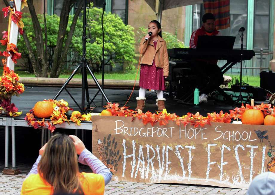 Celina Indira Casrellon, 7, sings Perfect by Ed Sheeran during Bridgeport Hope School's 7th Annual Harvest Festival at McLevy Green in downtown Bridgeport, Conn., on Saturday, Oct. 13, 2018. The event, which raises money for the school, included live music performed by Abe Deshotel and Friends, a raffle, arts and craft, food and even a costume parade by the students. Photo: Christian Abraham / Hearst Connecticut Media / Connecticut Post