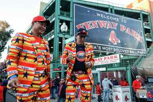 "Houston Astros fans Nguyen Le, left, and Jeremy ""Goob"" Howard stand outside Fenway Park as they arrive to Game 1 of the American League Championship Series on Saturday, Oct. 13, 2018, in Boston."