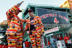 """Houston Astros fans Nguyen Le, left, and Jeremy """"Goob"""" Howard dance outside Fenway Park before Game 1 of the American League Championship Series on Saturday, Oct. 13, 2018, in Boston."""