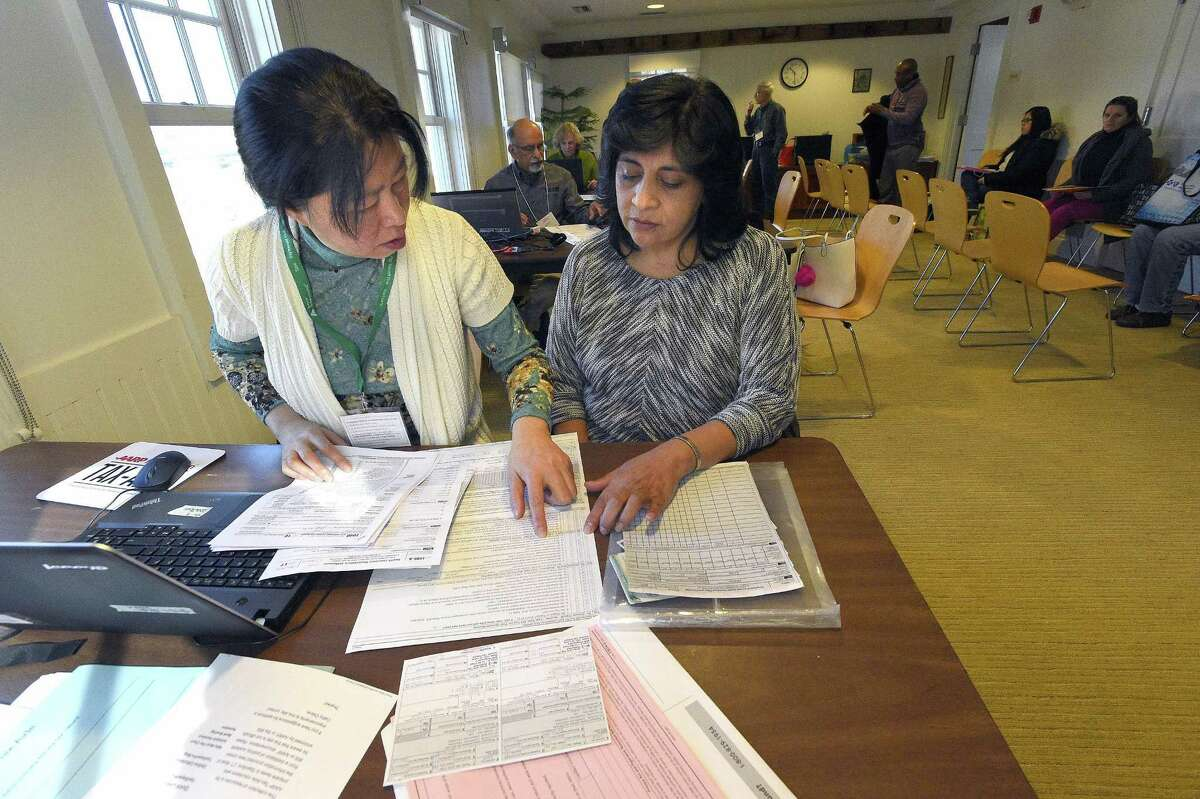 From left, Jie Hu, a trained tax counselor from AARP Tax-Aide, assists Marcia Reino of Stamford with preparing her federal and state income taxes on Saturday, March 17, 2018 at Springdale's Weed Memorial & Hollander Branch of the Ferguson Library in Stamford. The plan to eliminate the state income tax by Republican governor candidate Bob Stefanowski bring little relief to taxpayers in the bottom two-thirds of income groups.