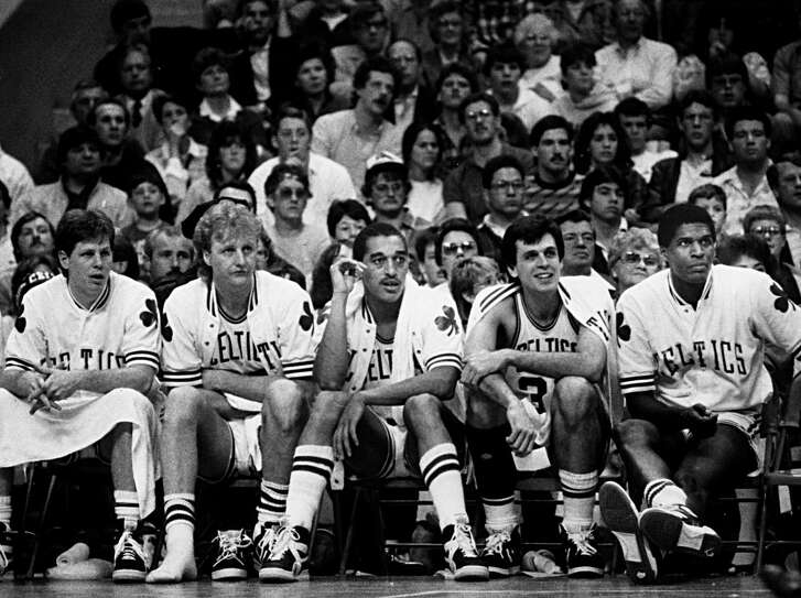 The Boston Celtics' 1985-86 championship starters, Danny Ainge, Larry Bird, Dennis Johnson, Kevin McHale and Robert Parish sit on the bench during a game against the New Jersey Nets at Boston Garden on April 13, 1986. (Photo by John Blanding/The Boston Globe via Getty Images)