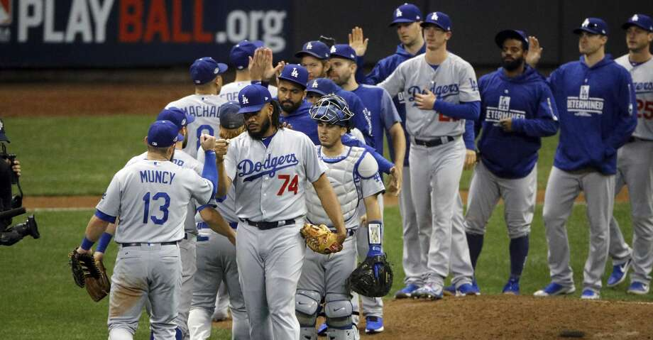 Los Angeles Dodgers players celebrate after Game 2 of the National League Championship Series baseball game against the Milwaukee Brewers Saturday, Oct. 13, 2018, in Milwaukee. The Dodgers won 4-3. (AP Photo/Charlie Riedel) Photo: Charlie Riedel/Associated Press