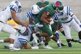 The Woodlands running back Bryeton Gilford (5) is brought down short of the first down maker during the first quarter of a District 15-6A high school football game at Woodforest Bank Stadium, Saturday, Oct. 13. 2018, in Shenandoah.