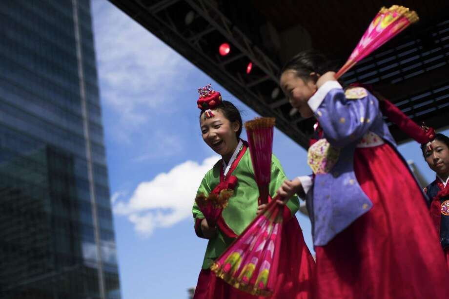 Seoul Baptist Church of Houston's folk dancers Elise Kwon and Hara We laugh as they step down from the stage after performing a fan dance wearing a hanbok during the Korean Festival Houston at the Discovery Green Park at 1500 McKinney, Saturday, Oct. 13, 2018, in Houston. Photo: Marie D. De Jesús, Houston Chronicle / Staff Photographer / © 2018 Houston Chronicle