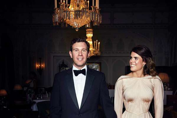 In this photo released on Saturday, Oct. 13 2018 by Buckingham Palace, Britain's Princess Eugenie of York and Jack Brooksbank are photographed at Royal Lodge, Windsor, England, ahead of the private evening dinner, following their Wedding, at St George's Chapel, Windsor Castle on Friday, Oct. 12, 2018. (Alex Bramall/Buckingham Palace via AP)