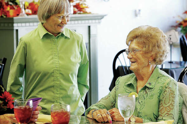 Virginia Kirkpatrick, right, founder and longtime executive director of Operation Blessing in Wood River, chats with her replacement, Karen Wilson, left, at a recent party held in Madison's Tea Room in Wood River to celebrate Kirkpatrick's retirement, after 36 years of service, and 90th birthday.