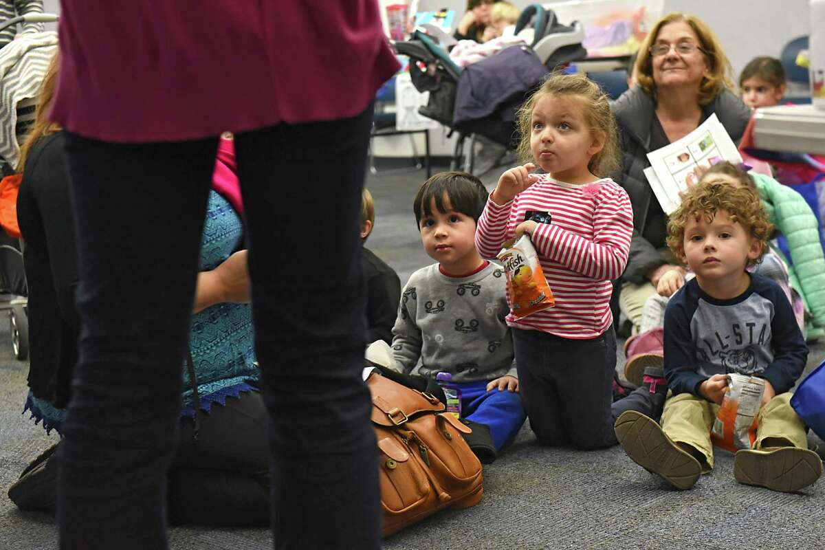 From left, Lou Cicchetti, 3, of Altamont, Amelia Tice, 5, of Guilderland and Maxwell Person, 3, of Slingerlands listen as children's librarian Elisabeth Smith, left, gives instruction on keeping track of the number of books they read during the