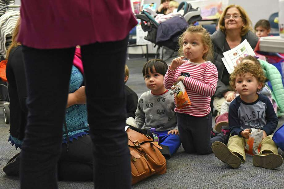 "From left, Lou Cicchetti, 3, of Altamont, Amelia Tice, 5, of Guilderland and Maxwell Person, 3, of Slingerlands listen as children's librarian Elisabeth Smith, left, gives instruction on keeping track of the number of books they read during the ""All Aboard to 1,000 Books Before Kindergarten!"" event at Guilderland Public Library on Friday, Jan. 20, 2017 in Guilderland, N.Y. (Lori Van Buren / Times Union) Photo: Lori Van Buren / 20039490A"
