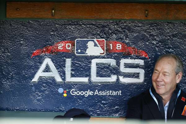 Astros owner Jim Crane sits in the Astros dugout before batting practice before Game 1 of the American League Championship Series at Fenway Park on Saturday, Oct. 13, 2018, in Boston.