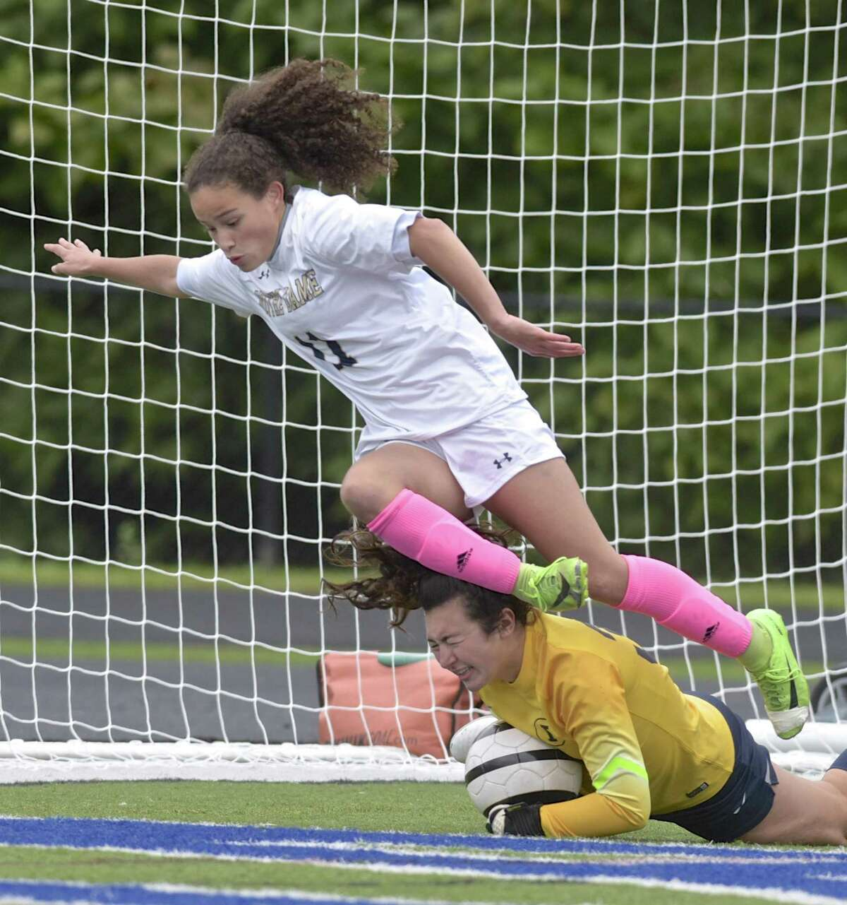 Note Dame's Toni Domingos (11) collides with Immaculate goalie Sophia Mingachos (32) as she makes a save in the girls soccer game between Notre Dame-Fairfield and Immaculate high schools, Saturday, October 13, 2018, at Immaculate High School, Danbury, Conn.