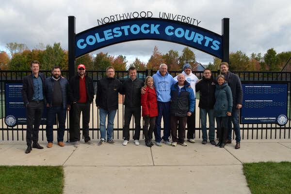 Longtime Northwood tennis coach Zane Colestock (sixth from right) poses along with several former NU tennis players outside of the recently refurbished and renamed Colestock Courts on Saturday morning.