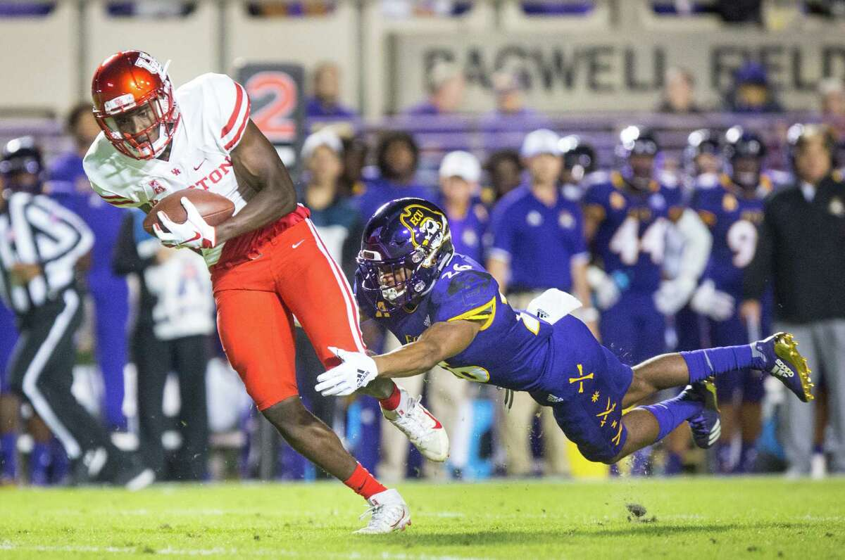 Houston's Courtney Lark, left, escapes East Carolina's Colby Gore and takes the ball for a touchdown during their game on Oct. 13, 2018 at Dowdy-Ficklen Stadium.