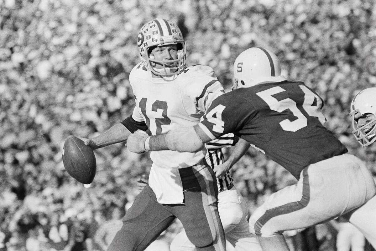 PALO ALTO, CA - NOVEMBER 22: Joe Roth #12 of the California Golden Bears attempts a pass during the 1975 Big Game against Stanford University played on November 22, 1975 at Stanford Stadium in Palo Alto, California. Rich Merlo #54 of Stanford rushes Roth. (Photo by David Madison/Getty Images)