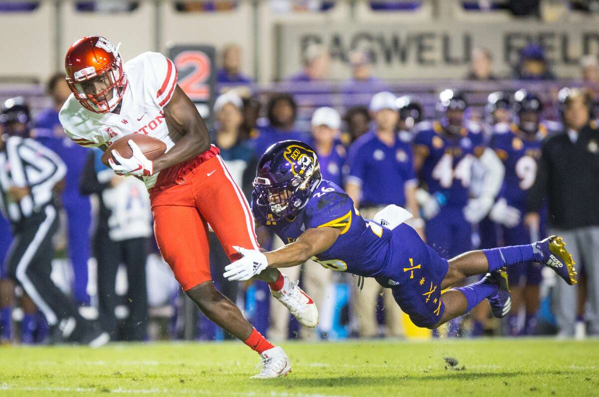 Houston's Courtney Lark, left, escapes East Carolina's Colby Gore and takes the ball for a touchdown during their game on Oct. 13, 2018 at Dowdy-Ficklen Stadium. (Molly Mathis/The Daily Reflector)