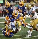 UCLA's Joshua Kelley (27) is tackled by California's Jordan Kunaszyk (59) and Elijah Hicks during the second half of an NCAA college football game Saturday, Oct. 13, 2018, in Berkeley, Calif. (AP Photo/Ben Margot)