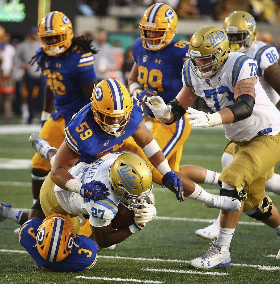 UCLA's Joshua Kelley (27) is tackled by California's Jordan Kunaszyk (59) and Elijah Hicks during the second half of an NCAA college football game Saturday, Oct. 13, 2018, in Berkeley, Calif. (AP Photo/Ben Margot) Photo: Ben Margot / Associated Press