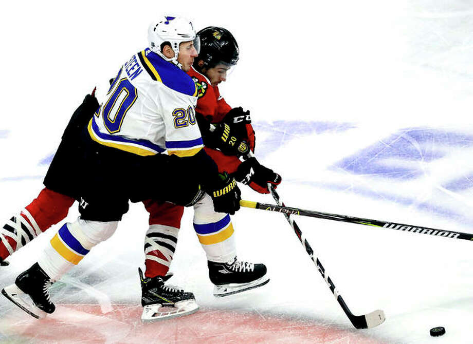 Blues left wing Alexander Steen, left, and Chicago Blackhawks center Nick Schmaltz battle for the puck Saturday night in Chicago. Photo: AP