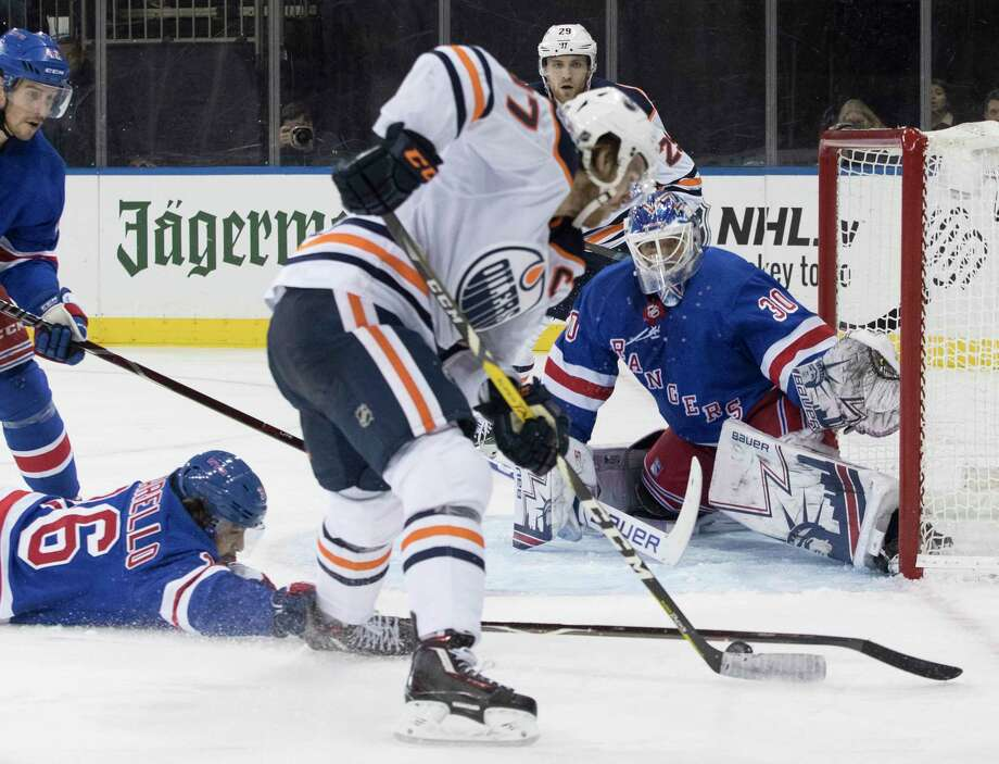 Edmonton Oilers center Connor McDavid (97) shoots the puck to score past New York Rangers right wing Mats Zuccarello (36) and goaltender Henrik Lundqvist (30) during the third period of an NHL hockey game, Saturday, Oct. 13, 2018, at Madison Square Garden in New York. The Oilers won 2-1. (AP Photo/Mary Altaffer) Photo: Mary Altaffer / Copyright 2018 The Associated Press. All rights reserved.