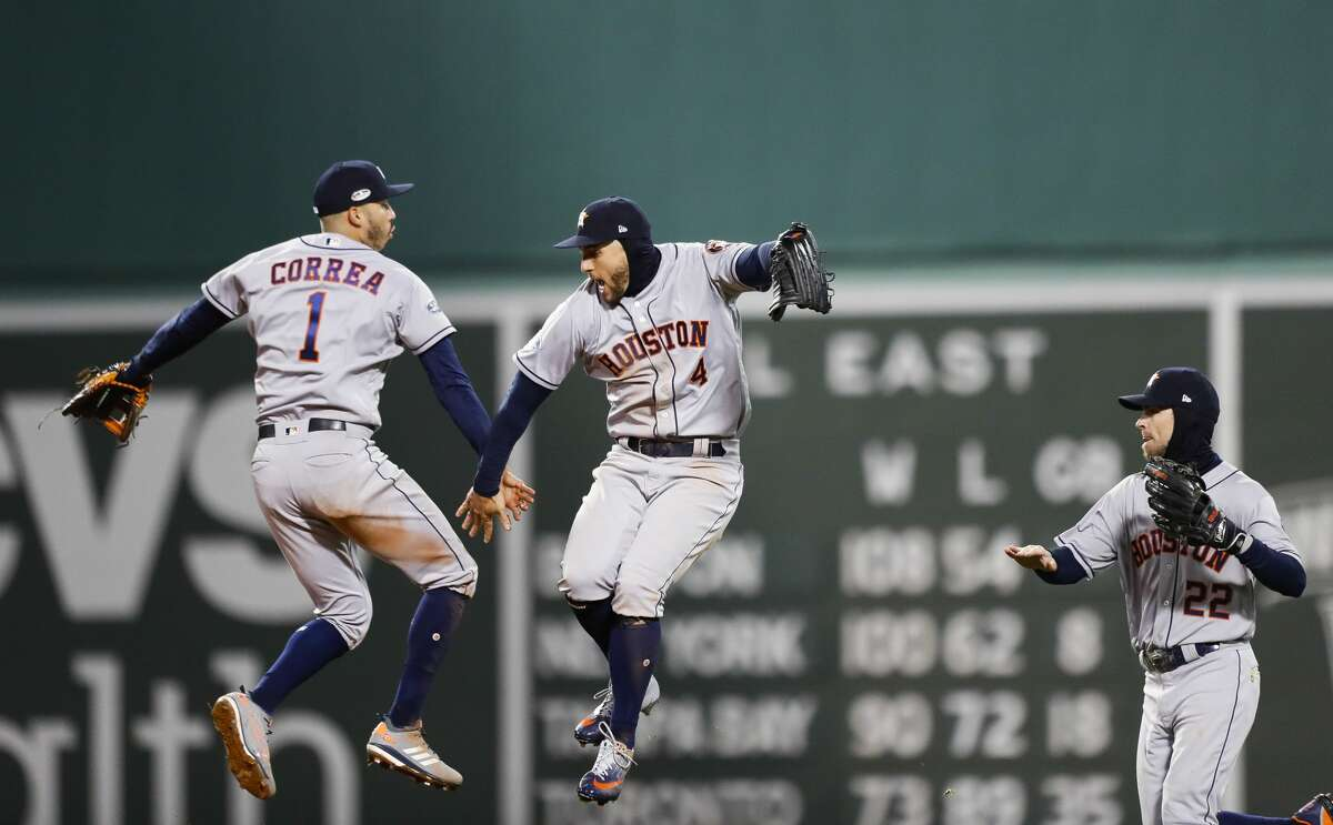 Houston Astros Carlos Correa (1), George Springer (4) and Josh Reddick (22) celebrate the Astros 7-2 win in Game 1 of the American League Championship Series at Fenway Park on Saturday, Oct. 13, 2018, in Boston.