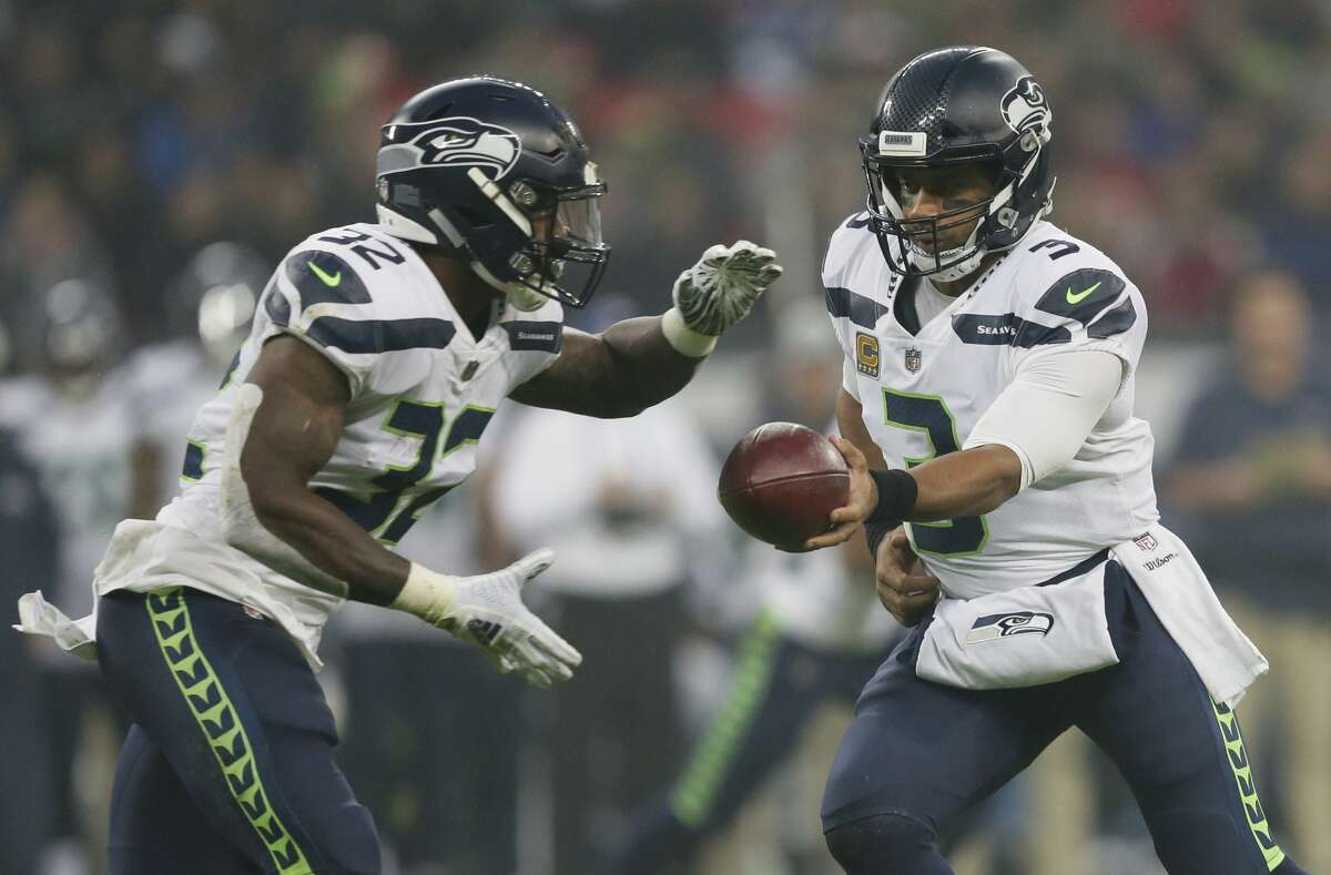 Seattle Seahawks quarterback Russell Wilson (3) hands off to running back Chris Carson (32) during the first half of an NFL football game against Oakland Raiders at Wembley stadium in London, Sunday, Oct. 14, 2018. (AP Photo/Tim Ireland)