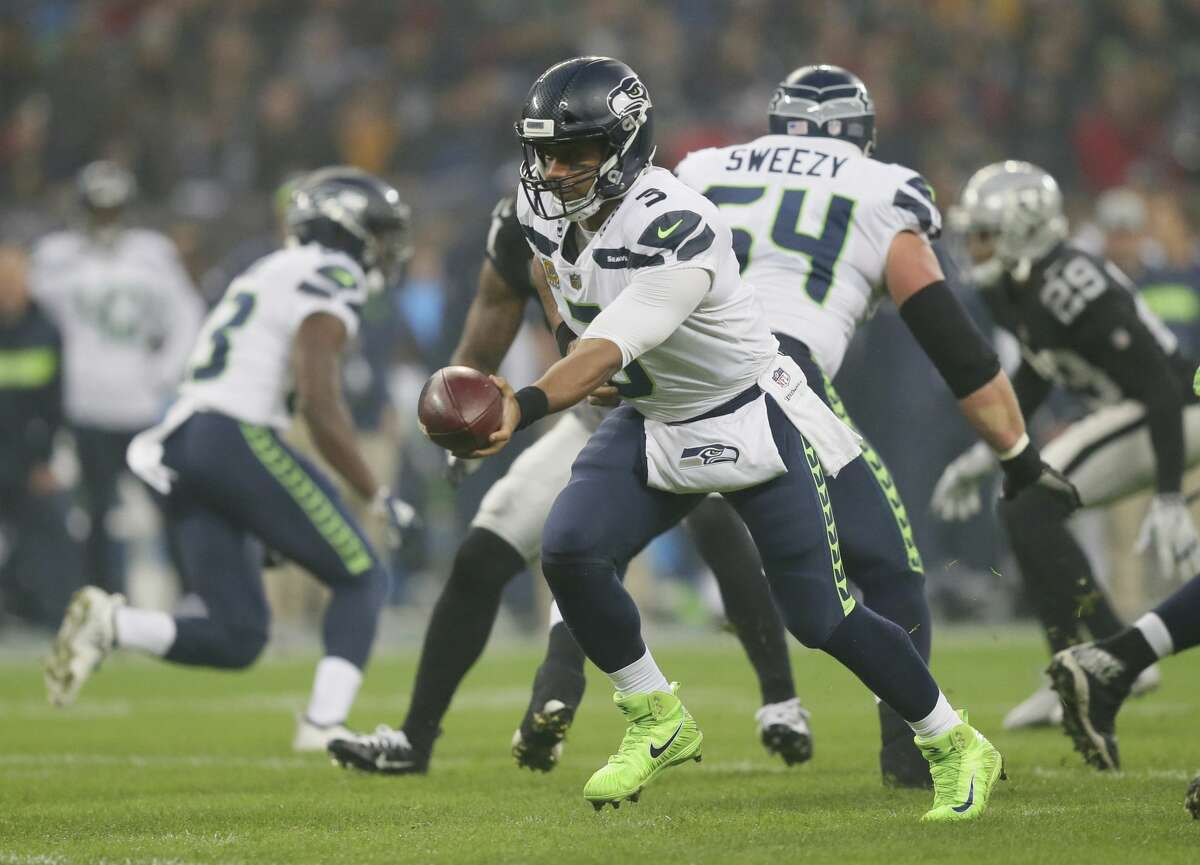 Seattle Seahawks quarterback Russell Wilson (3) hands off during the first half of an NFL football game against Oakland Raiders at Wembley stadium in London, Sunday, Oct. 14, 2018. (AP Photo/Tim Ireland)