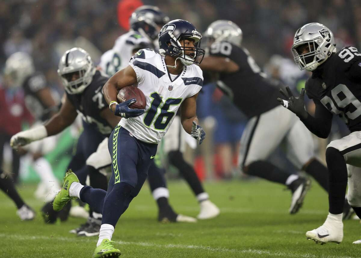 Seattle Seahawks wide receiver Tyler Lockett (16) runs with the ball during the first half of an NFL football game against Oakland Raiders at Wembley stadium in London, Sunday, Oct. 14, 2018. (AP Photo/Tim Ireland)