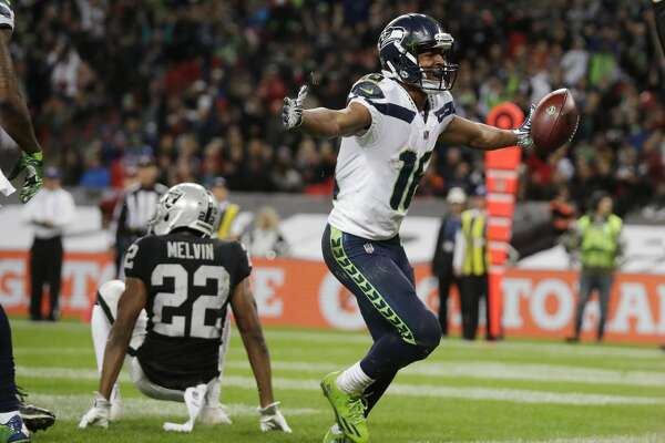 Seattle Seahawks wide receiver Tyler Lockett (16) celebrates after scoring a touchdown during the second half of an NFL football game against Oakland Raiders at Wembley stadium in London, Sunday, Oct. 14, 2018. (AP Photo/Matt Dunham)