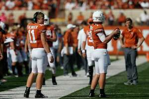 AUSTIN, TX - OCTOBER 13:  Sam Ehlinger #11 of the Texas Longhorns watches as Shane Buechele #7 warms up on the sideline in the first half against the Baylor Bears at Darrell K Royal-Texas Memorial Stadium on October 13, 2018 in Austin, Texas.