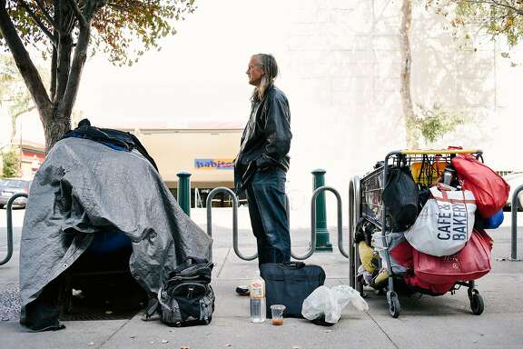Gene Paulson, who said he has been homeless for more than 20 years, stands next to his tarp covered shopping cart full of personal belongings, at left, as another person's cart is seen locked to a bike rack on the sidewalk in front of the Berkeley Public Library in Berkeley, Calif., on Thursday October 11th, 2018