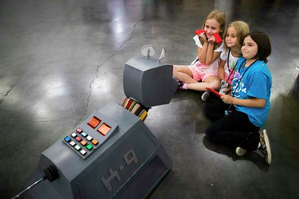 Ava Harris, 8, Lillian Harris, 5, and Cora Vrubel, 8, wait while Doctor Who's robotic companion K9 takes a photo of them together at the Houston Maker Faire, Sunday, Oct. 14, 2018, in Houston.