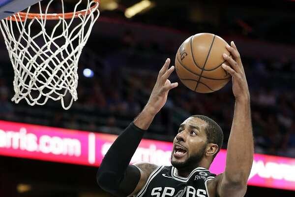 San Antonio Spurs' LaMarcus Aldridge (12) shoots as he gets past Orlando Magic's Mohamed Bamba during the second half of an NBA preseason basketball game, Friday, Oct. 12, 2018, in Orlando, Fla. (AP Photo/John Raoux)