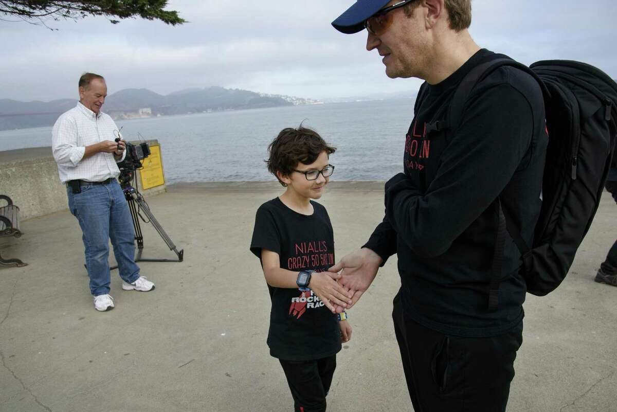 Niall McDermott slaps five with his dad Ryan McDermott after finishing his 50th 5K race in 50 days for charity at Crissy Field in San Francisco, Calif., on Sunday October 14th, 2018.
